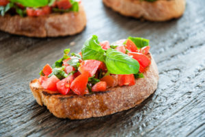 Italian tomato bruschetta with chopped vegetables herbs and oil on grilled or toasted crusty ciabatta bread